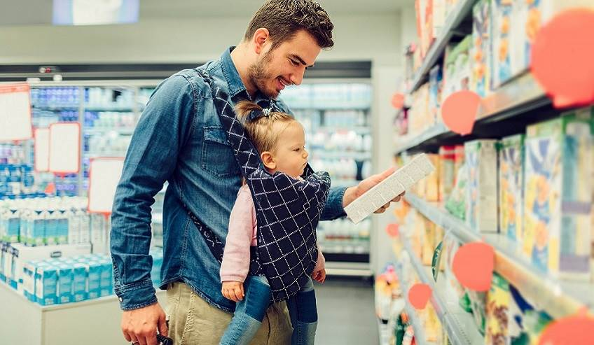 Man in grocery store with baby looking at packaged goods.